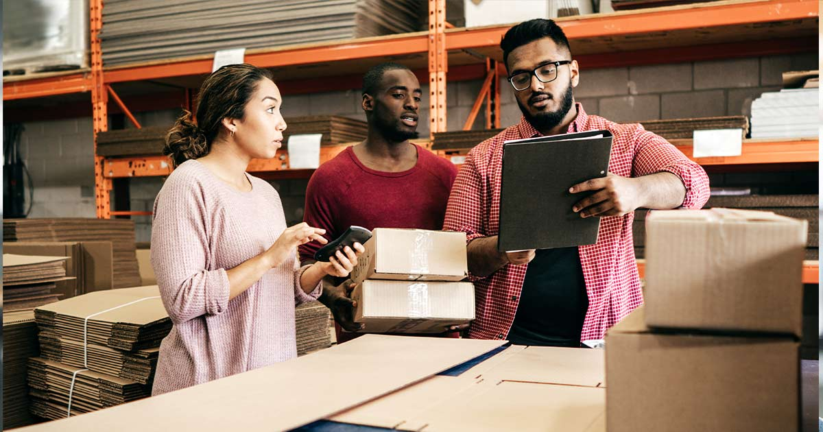 Three people discussing business in a warehouse