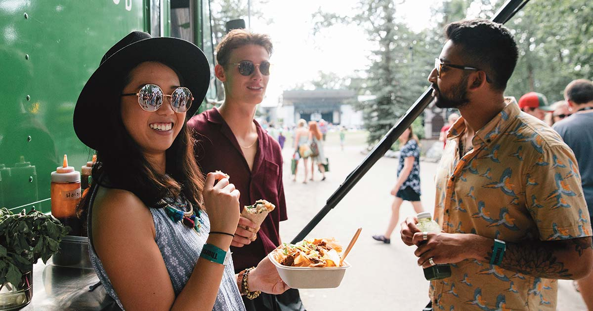 Three people in their twenties eating by a food truck