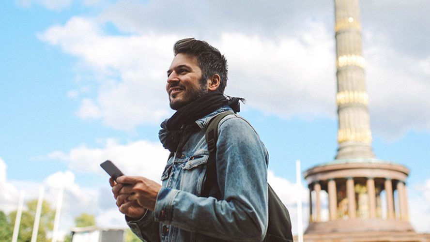Traveler using his phone in a new city