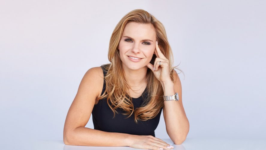 Michele Romanow leaning her elbows on a surface
