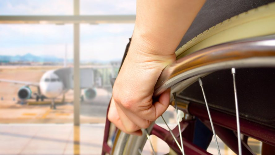 Close-up of a person's hand on their wheelchair wheel while looking at an airplane