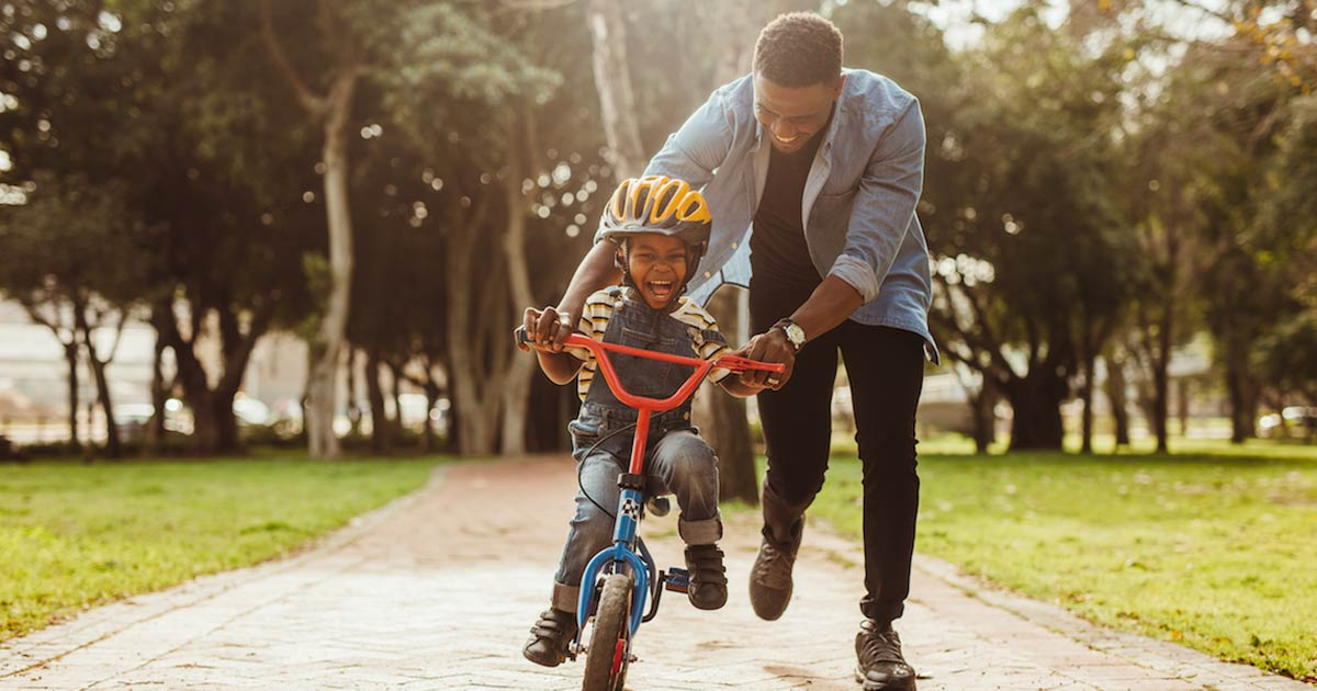 Dad helping young son ride his bike
