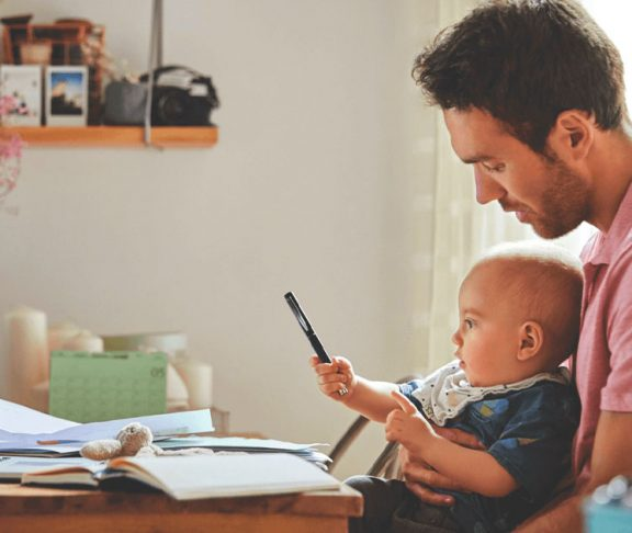 Father working from home as baby plays