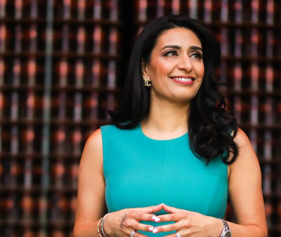 Manjit Minhas smiling and looking off-camera