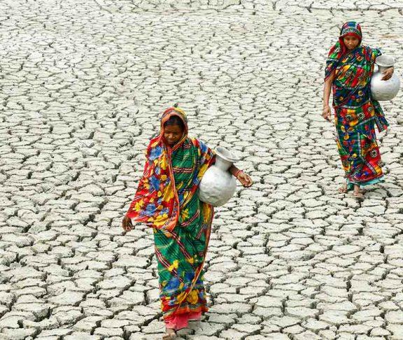 Women carrying jugs of water across dry land