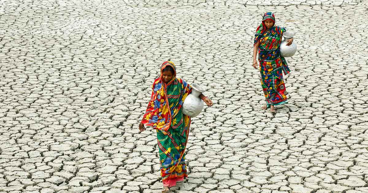 Women carrying jugs of water across dry land