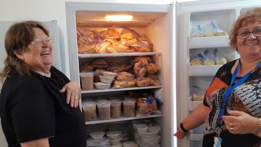 Legion volunteers showing off a fridge full of donated food