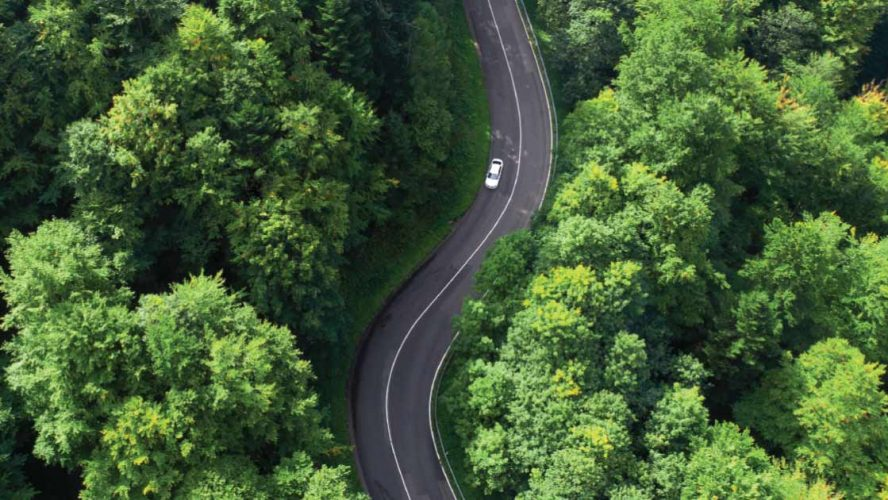 Aerial photo of a car driving down a road surrounded by forest