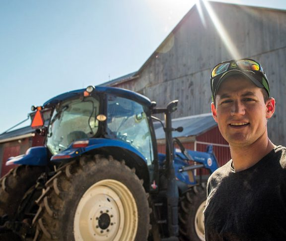 Andrew Campbell on a farm in front of a tractor and barn