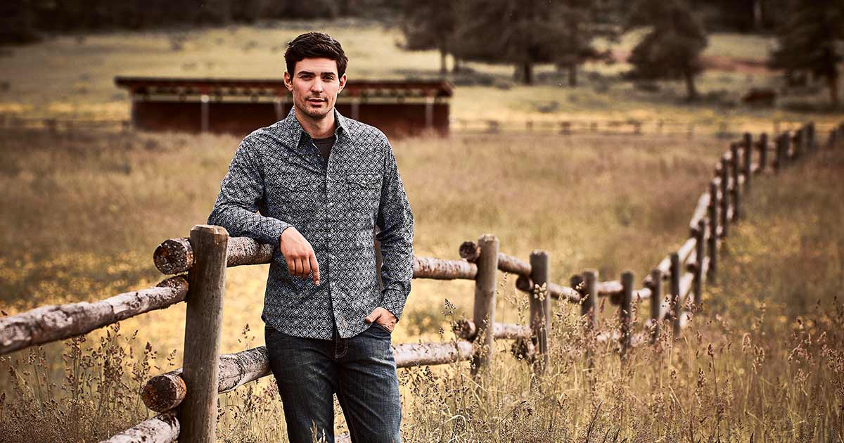 Carey Price leaning on a fence in a field