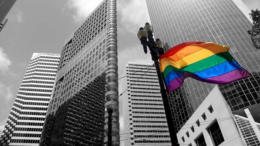 Greyscale city with multicoloured Pride flag flowing