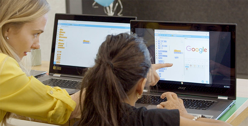 Lauren Howe helping a young girl learn on a computer