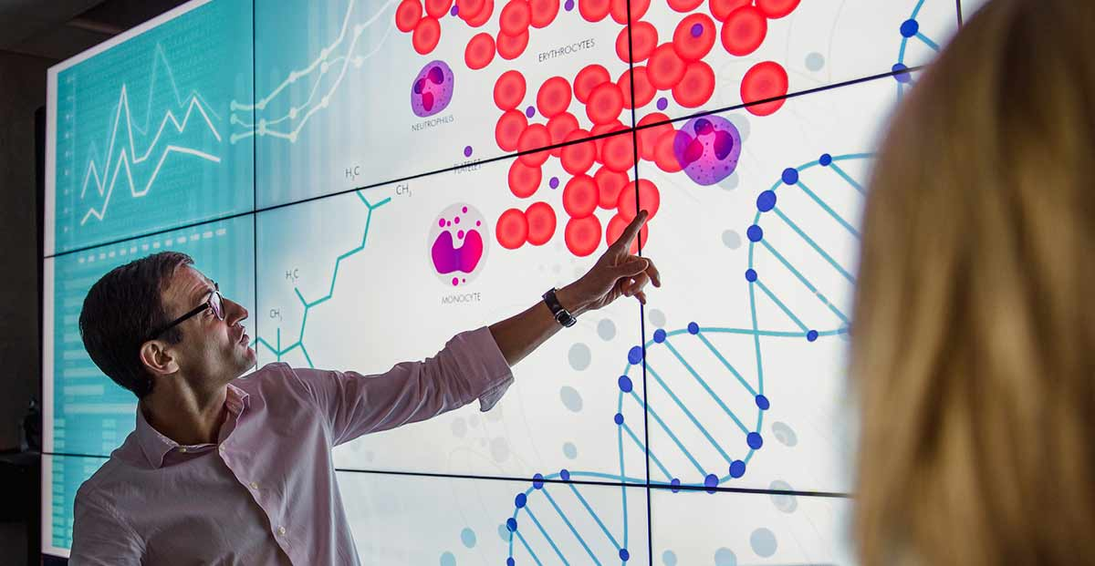 Man teaching and pointing at digital board depicting cells