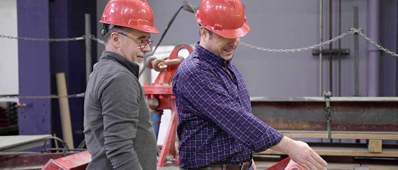 Two men wearing hard hats at Cornell