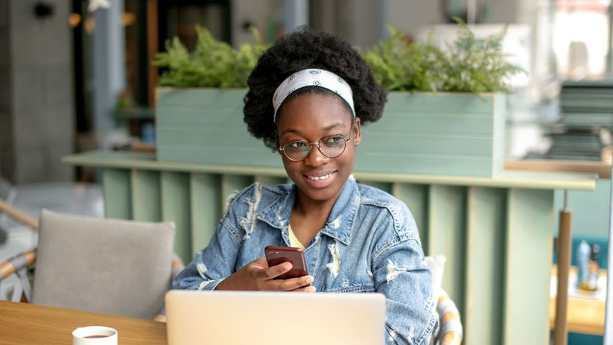 Young Black woman working at laptop and smiling