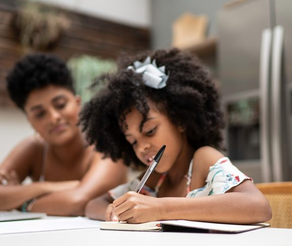 Young child writing in workbook with her mother