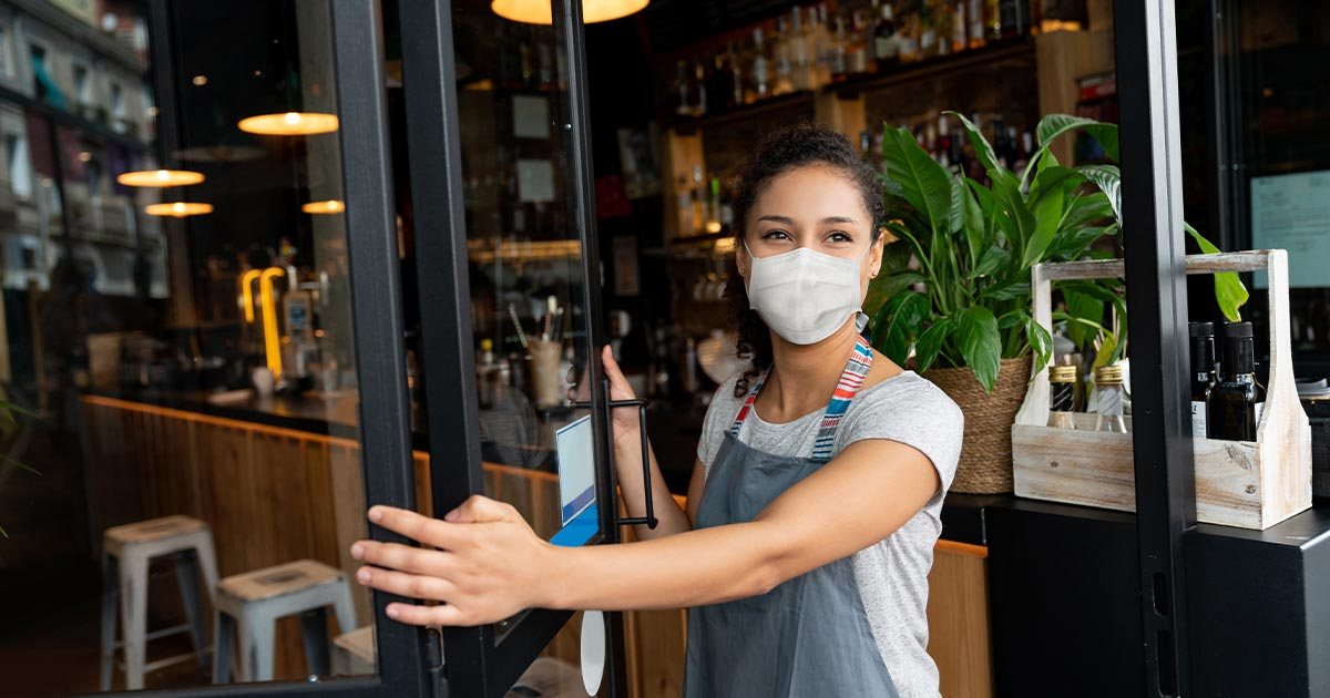 Woman business owner wearing a mask opening the door to her bar