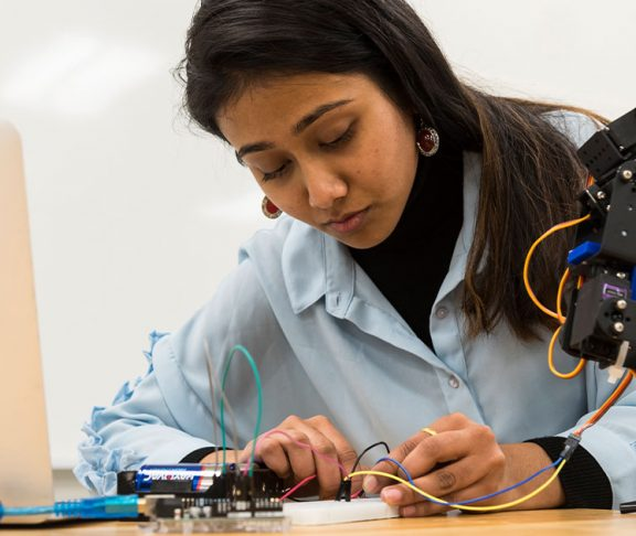 Algonquin College student working on a robotics project