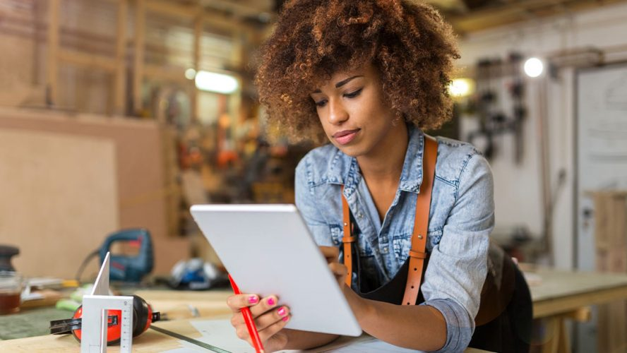 Black woman using digital tablet in her skilled trades workshop
