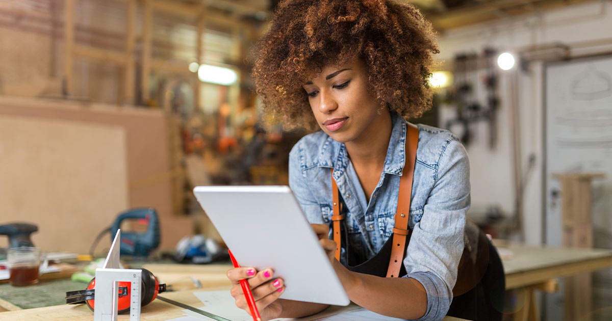 Black woman using digital tablet in her skilled trades workshop