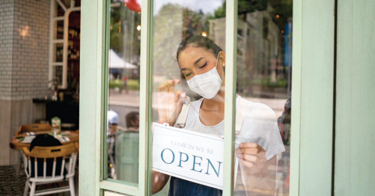Businesswoman wearing a mask setting the OPEN sign of her restaurant