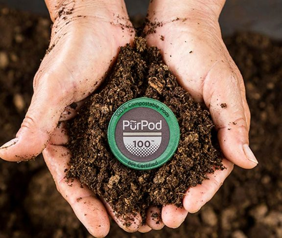 Cupped hands holding soil with a PurPod in the middle