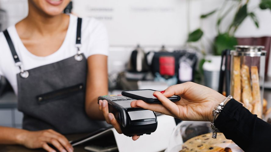 Customer paying by tapping their phone on payment system