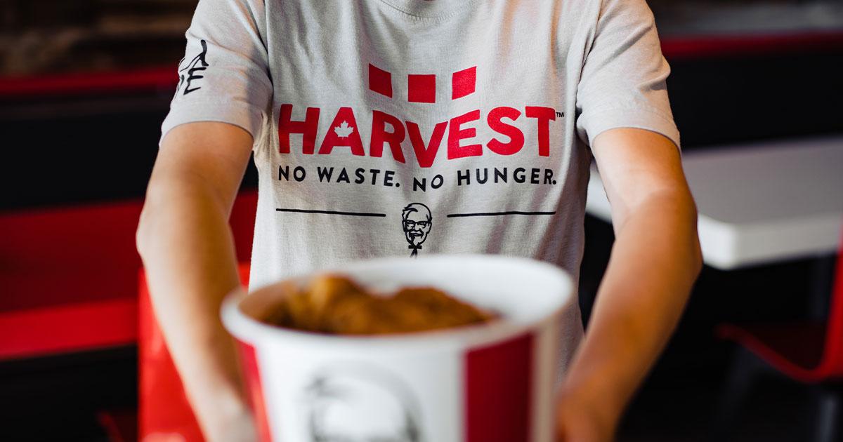 KFC Harvest volunteer holding a bucket of chicken