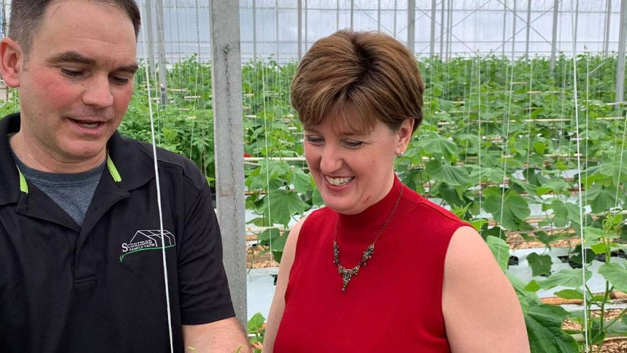 Minister Marie-Claude Bibeau speaking to a man in a greenhouse nursery