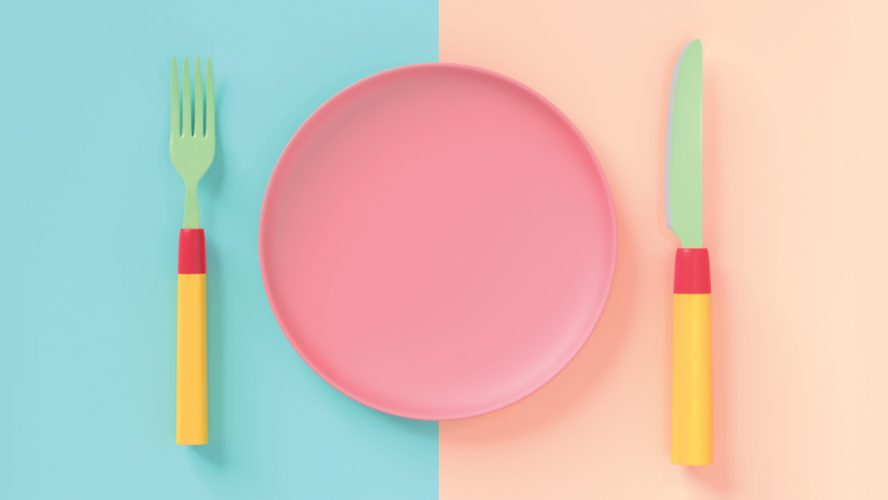 Pastel-coloured fork, plate, and knife laid on a table