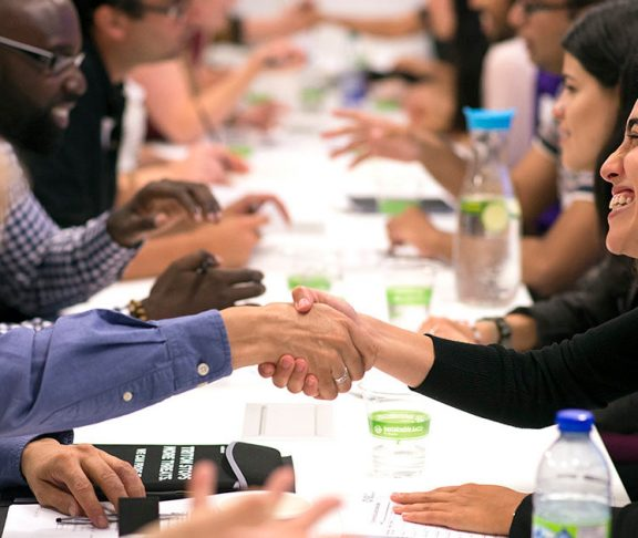People smiling and shaking hands across a table at a professional event