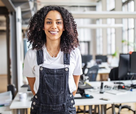 Smiling professional woman in an office wearing overalls