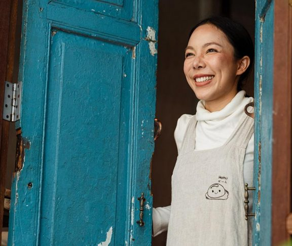 Smiling small business owner opening their doors