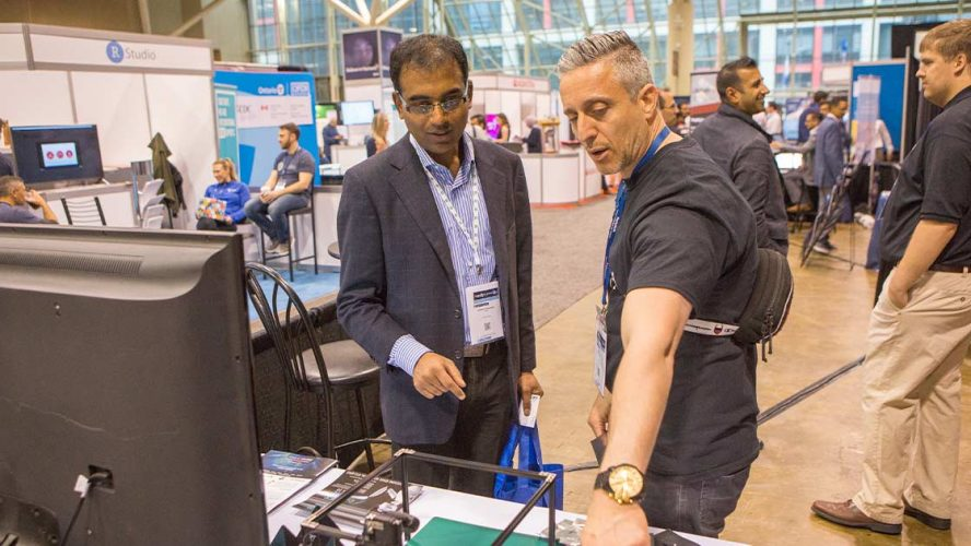 Two attendees of Big Data and AI Toronto checking out new tech