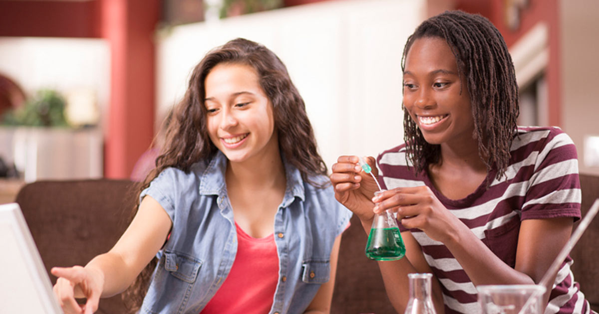 Two teen girls doing a science experiment at home