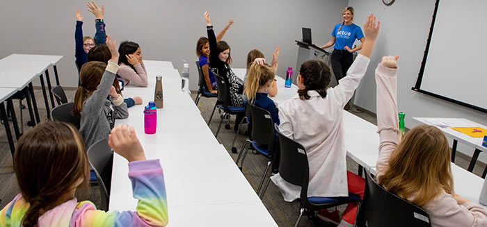 Young girls at Connections raising their hands in a STEM lesson