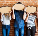 Youth holding speech bubbles in front of their faces