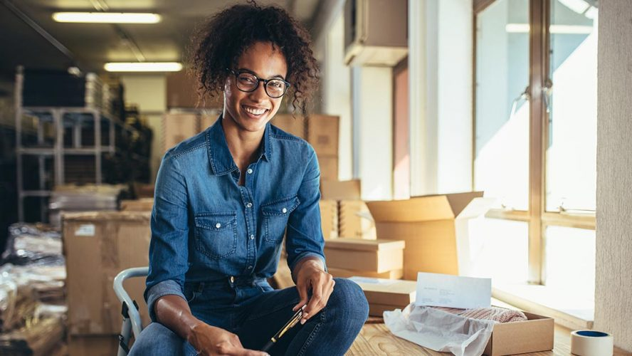 Black business owner setting up their office and smiling