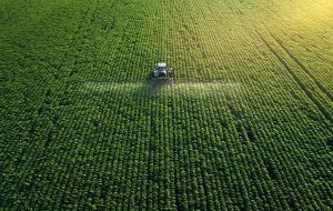 Aerial photo of a tractor tending to a large field of crops