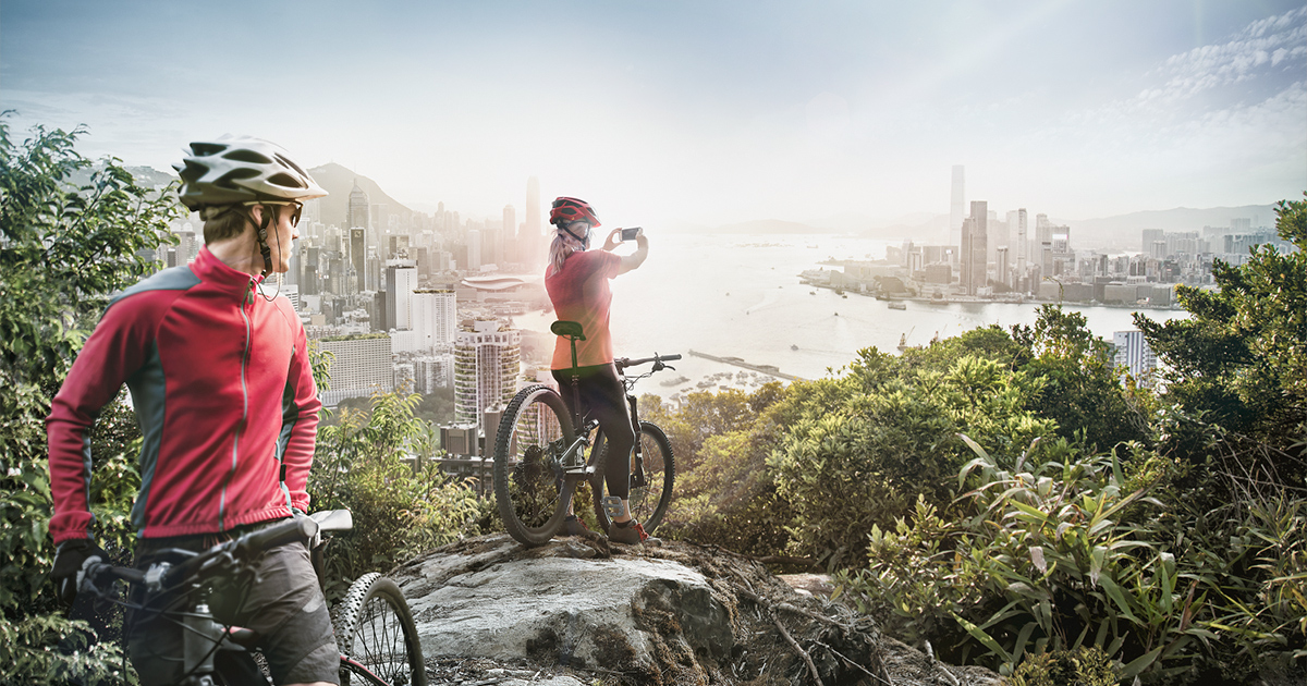 Couple on bikes taking picture of smart city