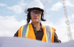 Female engineer looking at plans on a work site