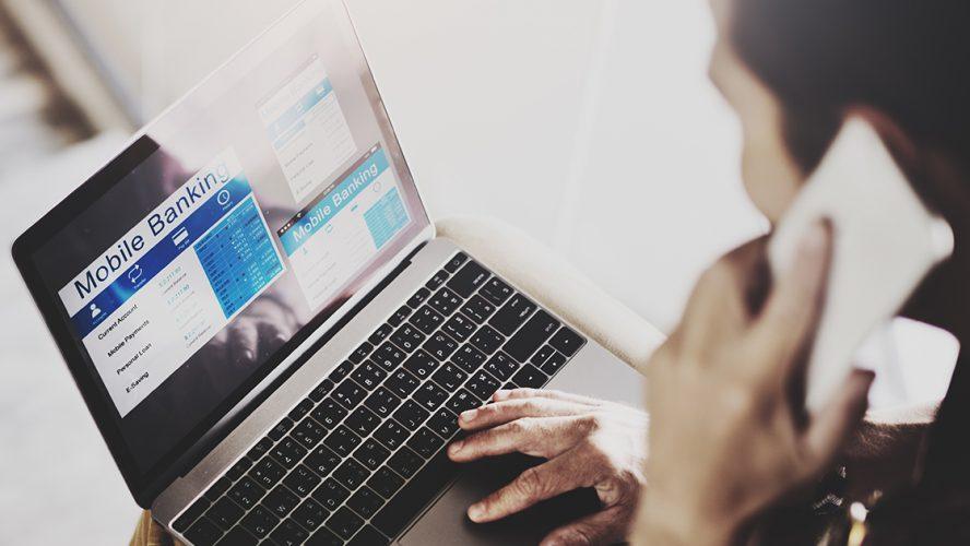 Man looking at online banking on laptop