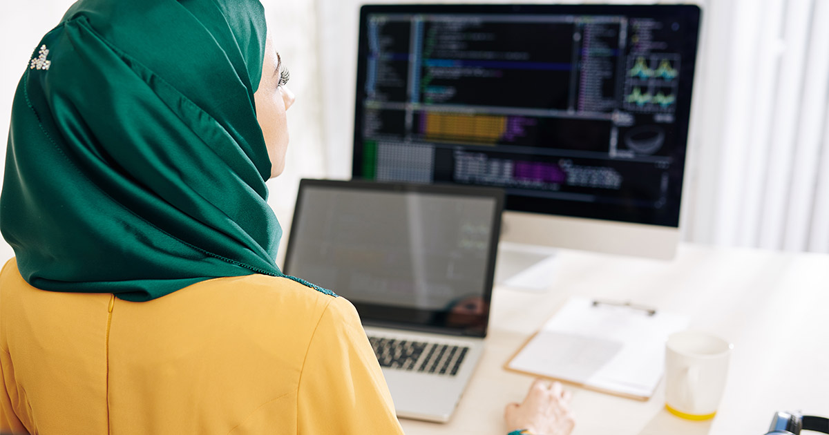 Woman in an emerald hijab programming on her computer