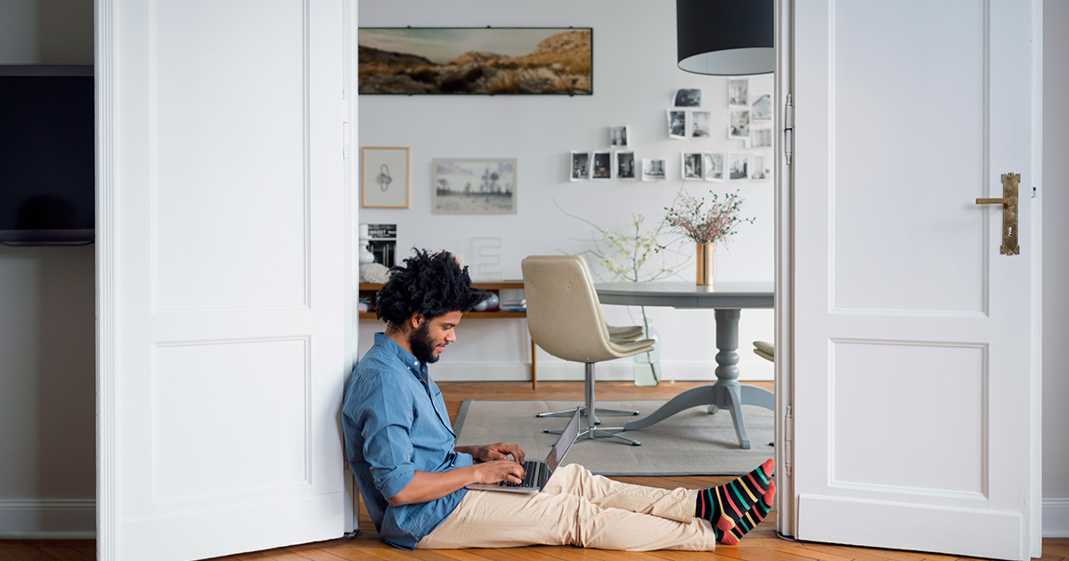 A man sitting on the floor and working on his laptop