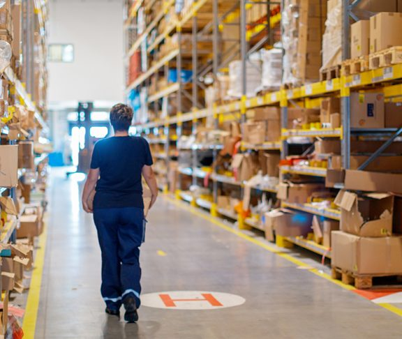 An employee carrying a package into a warehouse