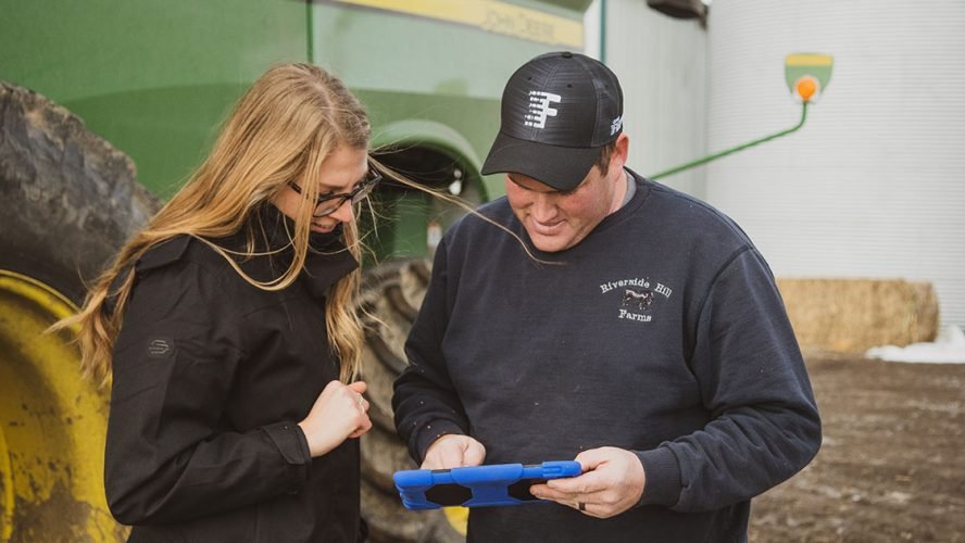 Two people using Climate FieldView technology on a tablet