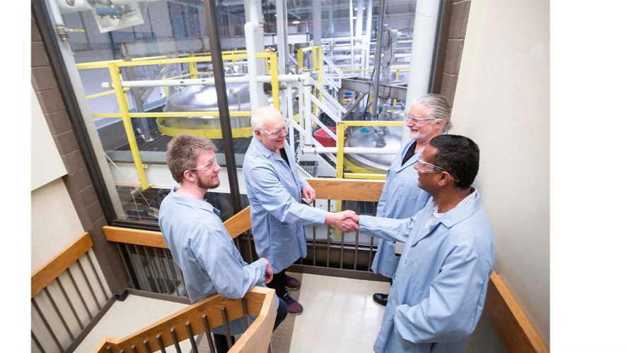 Four Scientists Conversing in a Stairwell Overlooking their Lab