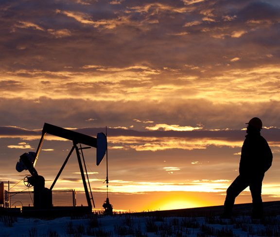 Oil worker staring into sunset