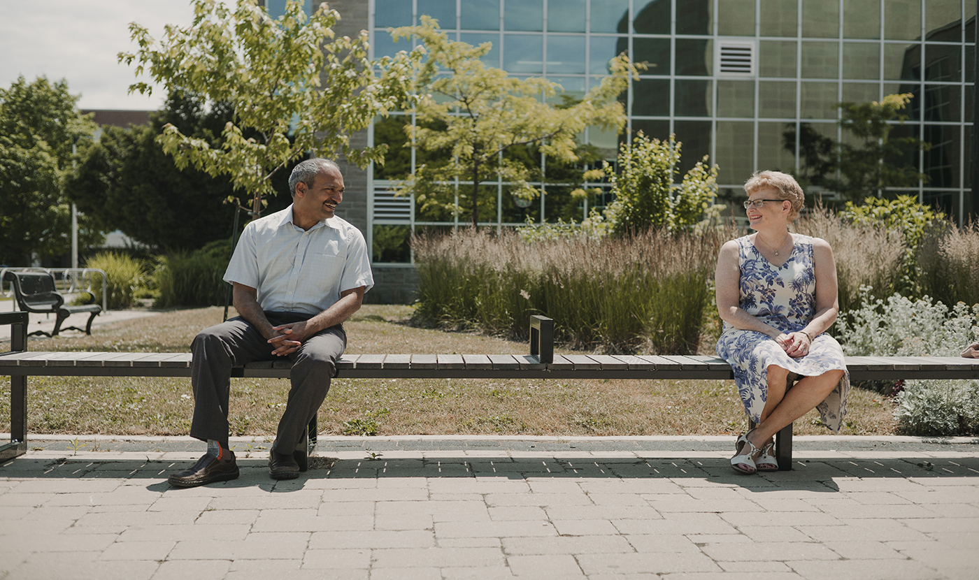 Ravi Allison, Man and Woman Sitting Across from Each Other on a Bench Enjoying Conversation