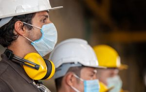 Workers wear protective face masks